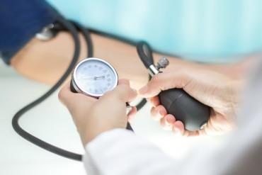 Doctor checking blood pressure with sphygmomanometer gauge in focus.