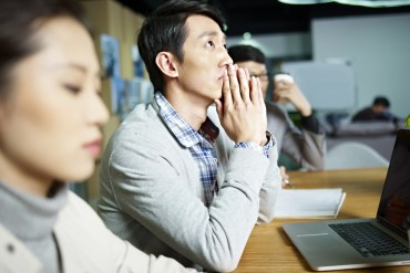 young asian businessman looking up and thinking during meeting in office.