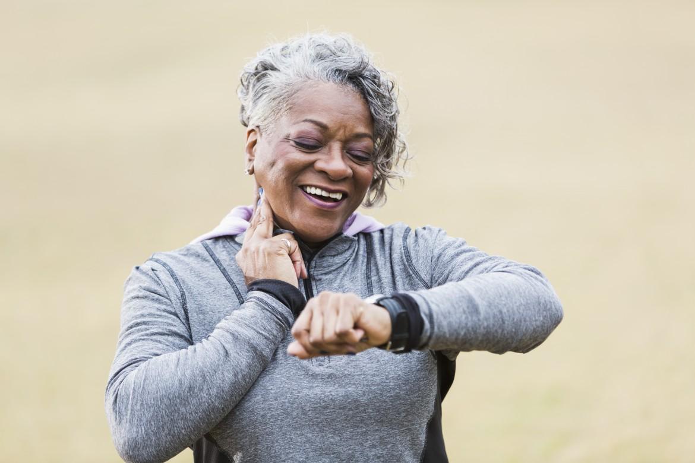 Senior woman exercising, taking pulse