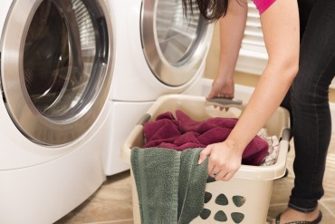 Domestic Life:  House wife removing towels from clothes dryer to Laundry basket