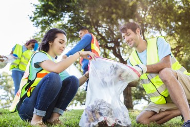 Happy community service people cleaning up local park. They are wearing bright yellow and orange vests. They have a trash bag and are filling is with trash they have found in the park. Their are two knealing down and two others behind them.