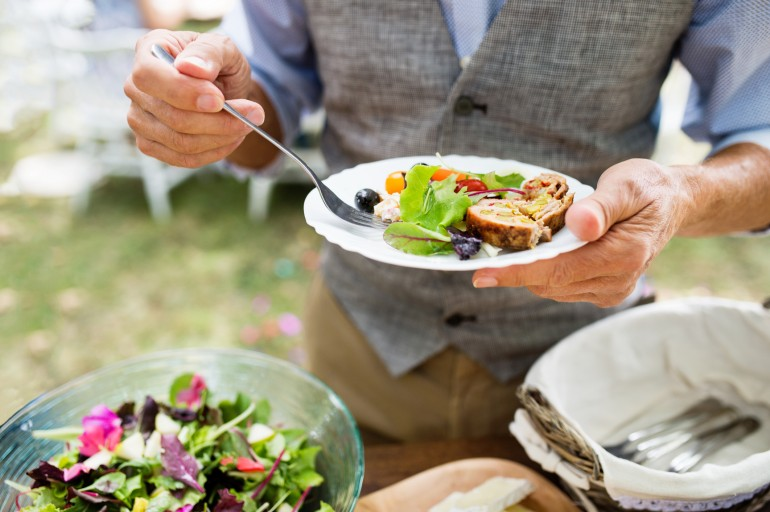 Unrecognizable man with a plate with food. Family celebration outside in the backyard. Big garden party.