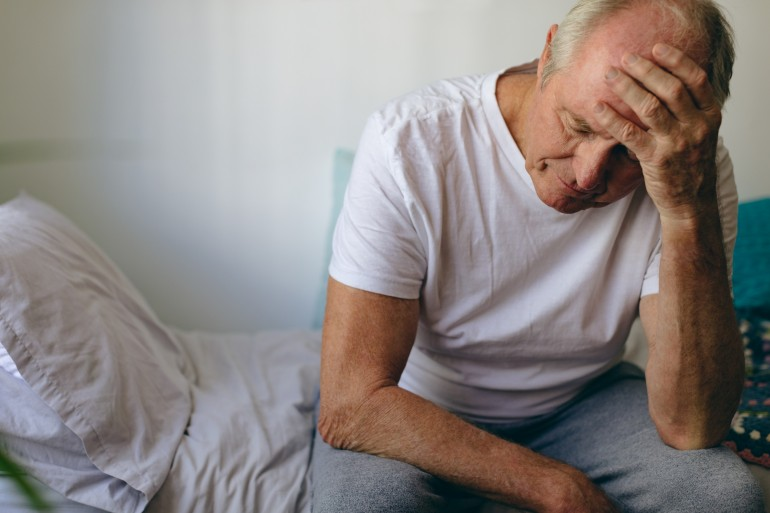 Front view of frustrated senior Caucasian  male patient sitting on bed at retirement home. He touches his forehead with hand.