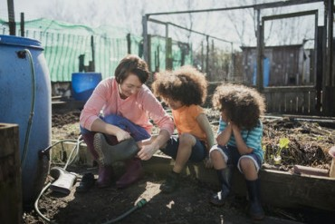 Two little boys are putting their wellies on at the allotment with help from their mum.