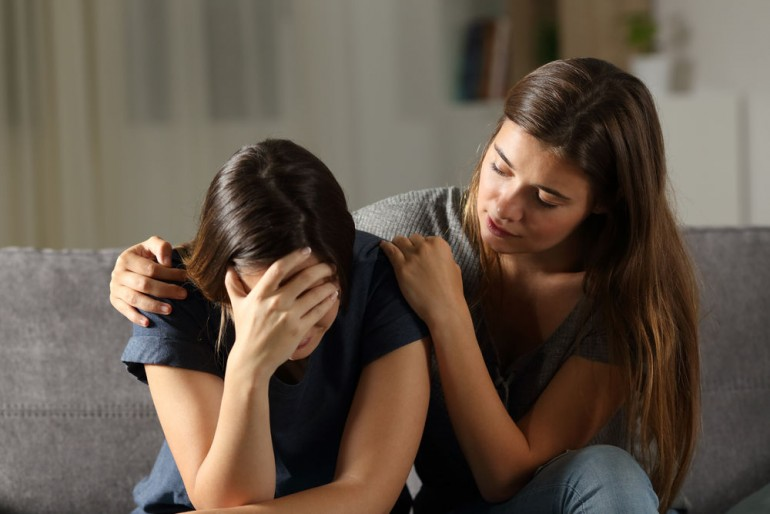 Teen comforting hes sad friend in the night sitting on a couch in the living room at home