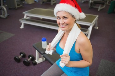 Festive brunette smiling at camera in fitness studio at the gym