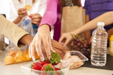 Multi ethnic teens  in kitchen making school lunches. These could be adopted or foster home teens.