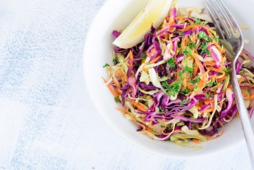 Top view of a white bowl of coleslaw salad with a fork
