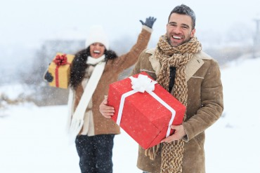 Young couple having fun with christmas presents on snow mountain