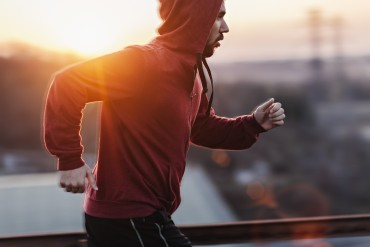 Photo of a man running while sun is setting