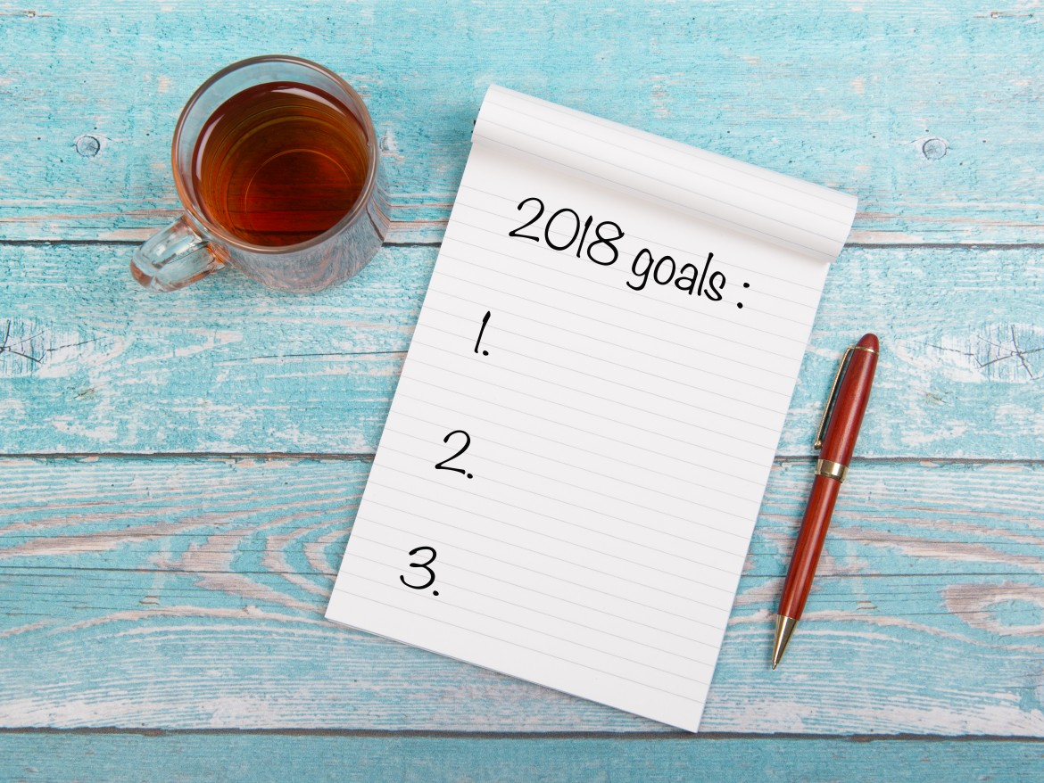 Notebook with new years goals for 2018 with a cup of thee and a pen on a blue wooden table seen from above