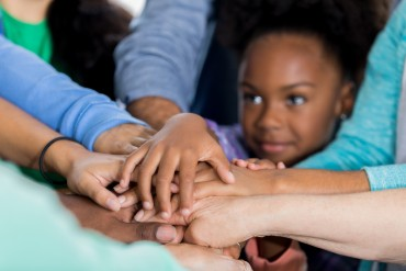 Adorable African American little girl smiles while putting her hands together with adult volunteers. She and others are volunteering at a charitable organization.