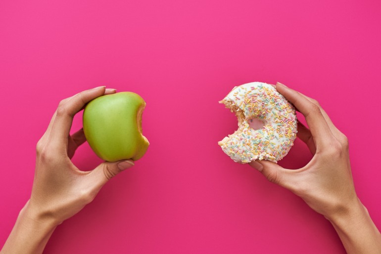 Dieting or good health concept. Young woman rejecting Junk food or unhealthy food such as donut or dessert and choosing healthy food such as fresh fruit or vegetable.