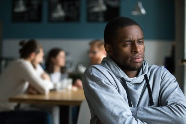 Frustrated excluded outstand african american man suffers from bullying or racial discrimination having no friends sitting alone in cafe, sad depressed black guy upset being rejected by white people