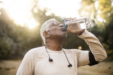 A senior African American Man enjoying refreshing water after a workout
