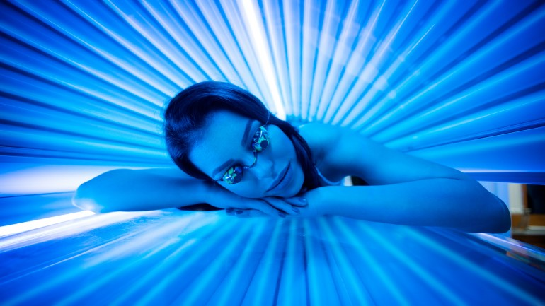 Attractive young woman tanning in solarium and smiling.