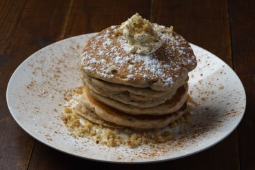 cinnamon walnut American style pancakes on white plate on wooden table