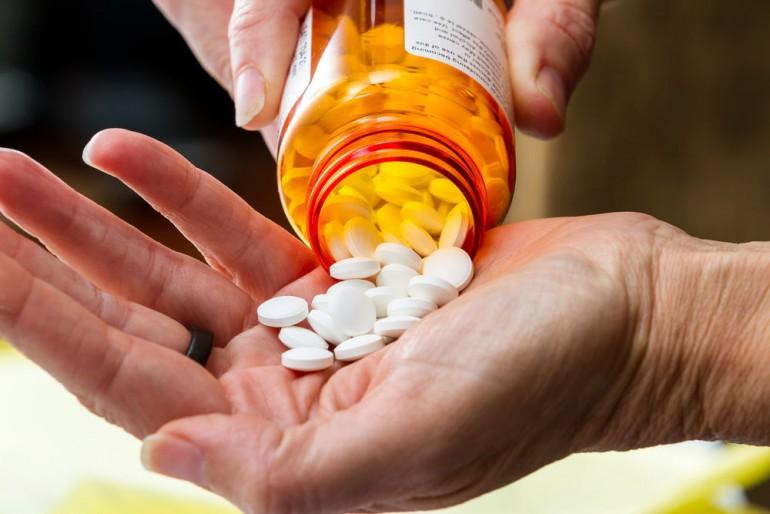 close up of a hand handling prescriptions pills as a concept