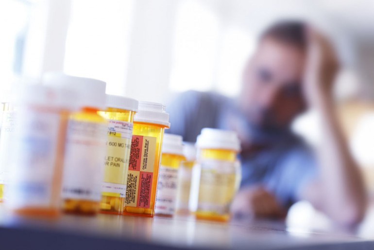 A large group of prescription medication bottles sit on a table in front of a distraught man who is leaning on his hand as he sits at his dining room table.  The image is photographed with a very shallow depth of field with the focus being on the pill bottles in the foreground.