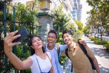 Multi-ethnic group of friends taking selfie pictures on street