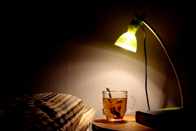 Bedside table with lamp, book and a cup of tea. Going to bed concept.